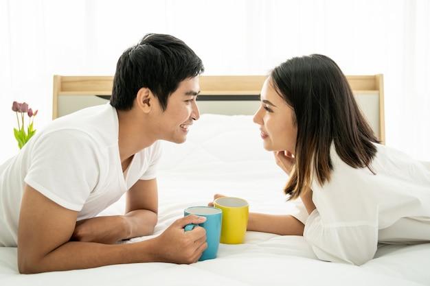 寝室、レジャー、カップル、関係、バレンタインの朝にコーヒーと一緒に楽しんでいるアジアの若いカップル。コピースペース付きの写真