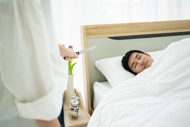 Жена держит нож и целится в мужа, который спит на кровати. семейная проблема и развод.