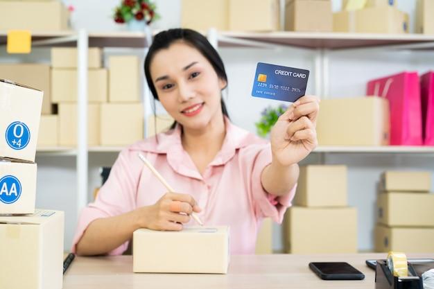 電子商取引やオンラインショッピング、偽のクレジットカードを見せて幸せな女性の美しい若いアジア女性。