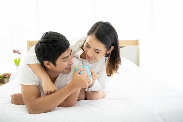 朝、レジャー、カップル、関係、バレンタインの悪い部屋でコーヒーを一緒に楽しんでいるアジアの若いカップル。