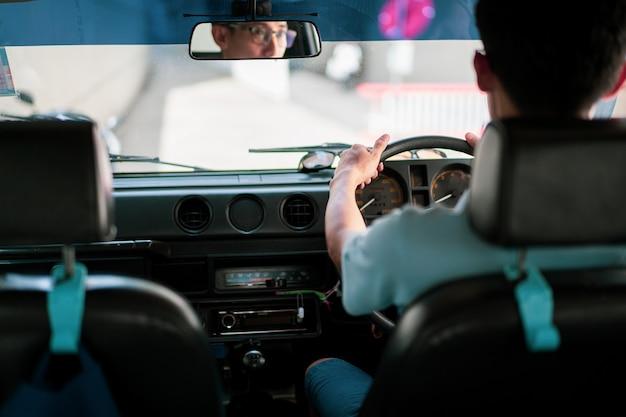 Азиатский водитель управляя винтажным автомобилем и смотря назад от зеркала. фотография с копией космической сцены.