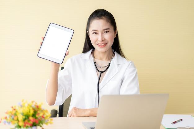 空の白い画面でデジタルタブレットを示す美しい若いアジア医師をクローズアップ。