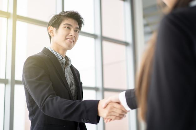 ビジネスマンやビジネスウーマンは、ビジネストークの後に握手をしています。プロのビジネスマンの概念。