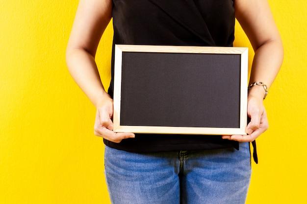 Девушка держа малый деревянный конец черной доски вверх.