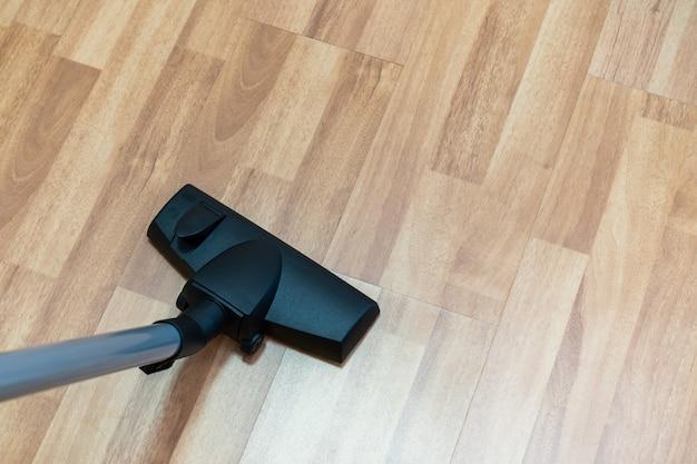 掃除機を使用して木の床を掃除する家政婦。