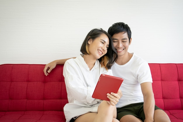 Азиатские молодые пары сидя на красной софе в живущей комнате и используя цифровой конец таблетки вверх.