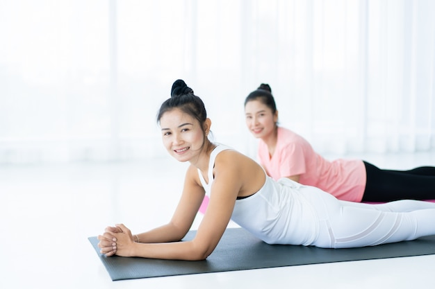 ヨガを一緒に行う女性は、毎日のライフスタイルで健康、健康的な生活、健康的な活動の概念を行使します。
