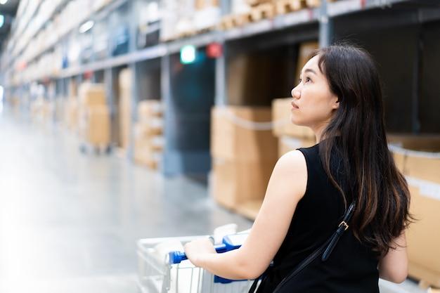 Портрет красивой азиатской женщины в складе. азиатская женщина ищет детали на полке крупным планом.