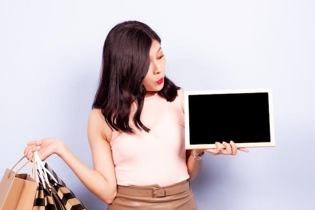 ブラックボードとショッピングバッグを示す概念をショッピングで美しく、かわいいアジアの女の子をクローズアップ。