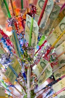 Тайский буддист делает заслугу с банкнотой на фестивале сонгкран. фестиваль сонгкран - традиционный новогодний праздник в таиланде.