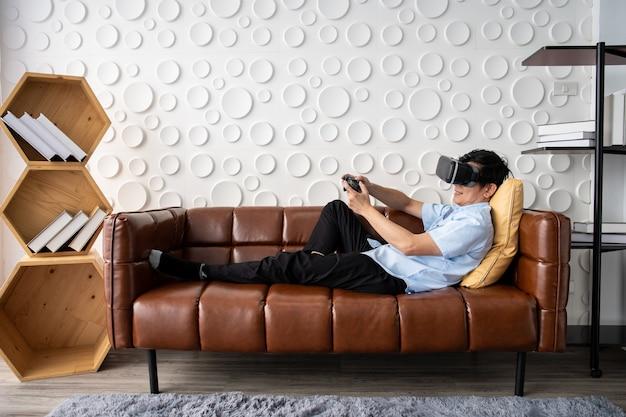 リビングルームでバーチャルリアリティのゴーグルを使用してビデオゲームをプレイするアジアの成人男性