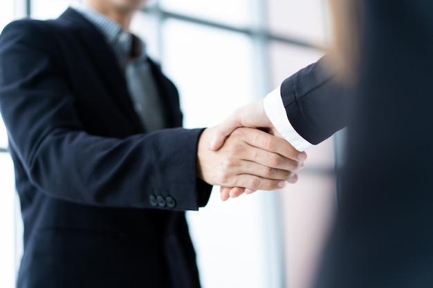商談後の握手を行うビジネス人々