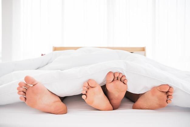 一緒にベッドで寝ている若いアジアのカップル