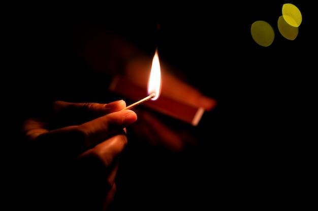 Мужчина держит горящую спичечную палку в темноте