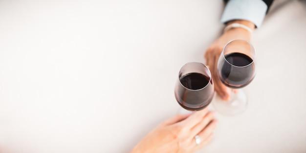 レストランで一緒にお祝いし、赤ワインを飲む夫と妻