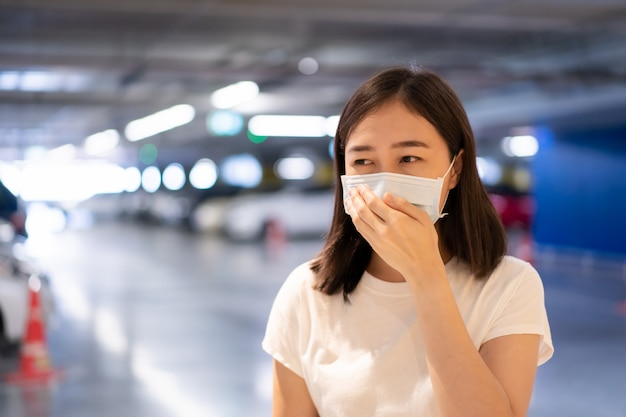 Потревоженная азиатская женщина нося защитную маску