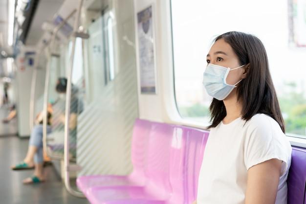 Красивая молодая азиатская женщина нося защитную маску