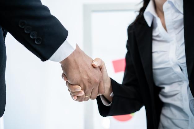 Азиатские и кавказские этнические предприниматели делают рукопожатие вместе после того, как сделано и завершено деловые переговоры. доверьтесь деловому партнерству и коллеге. успешный в бизнес-концепции.