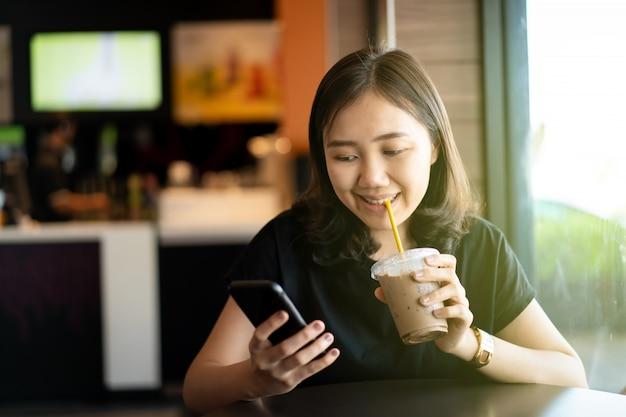 コーヒーショップやレストラン、よそ見女性に座って美しい幸せなアジア女