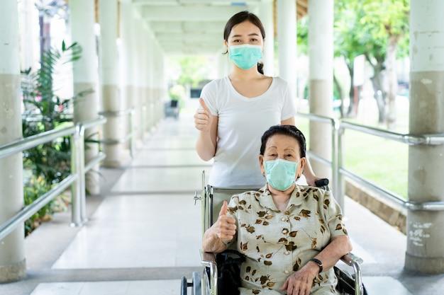Молодой азиатский внук заботясь о ее бабушке сидя на кресло-коляске.