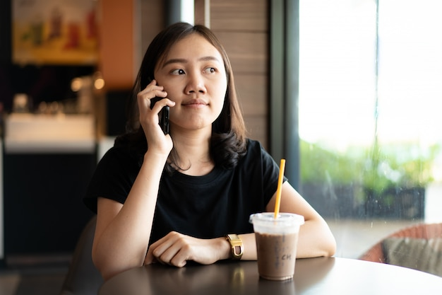 アジア民族の若い女性はリラックスして、コーヒーショップでアイスコーヒーを飲み、電話で話して