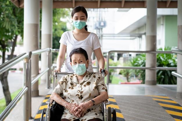 車椅子に座っている彼女の祖母の世話をする若いアジアの孫。コロナウイルスによる防護マスクを着ている人