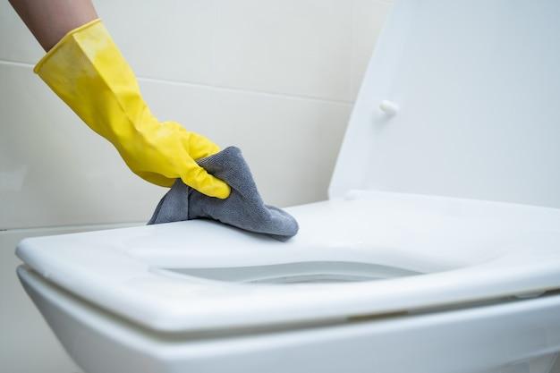 Горничная моет смываемый унитаз с помощью спирта и жидкого моющего раствора. санитария и здравоохранение.