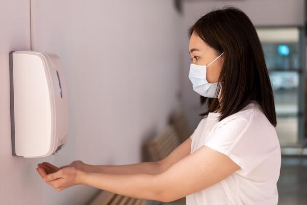 病院にいる間に防護マスクでマスクされ、洗浄と衛生のために手に液体アルコールスプレーを使用しているアジアの若い女性。