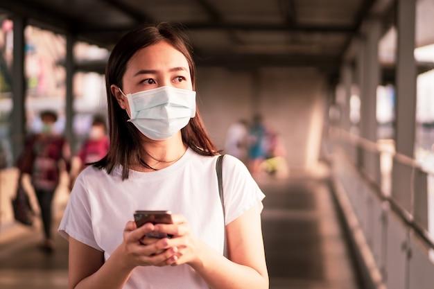 Красивая молодая азиатская женщина нося защитную маску пока путешествующ в городе