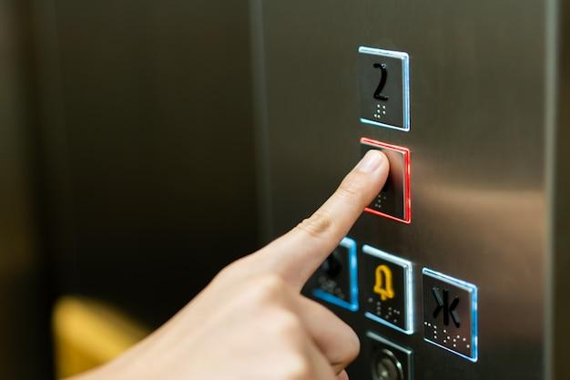 Люди нажимают кнопку в лифте и выбирают первый этаж с помощью указательного пальца.