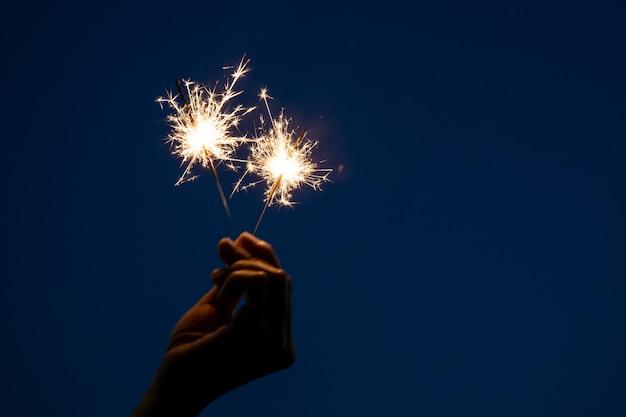 女の子は、クリスマスとお正月祭で祝う小さな線香花火手花火で遊んでお楽しみください。