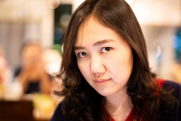 アジアの美しい女性の肖像画は、コピースペースとぼやけた壁にクローズアップ。