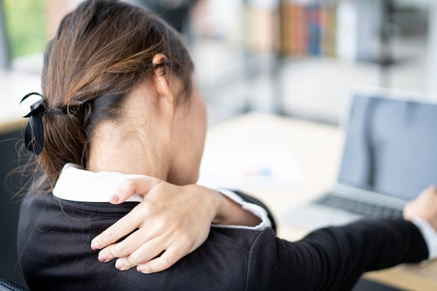 勤勉なオフィスのアジア女性実業家。オフィス症候群と仕事中毒のオフィスの人々の概念。健康上の問題があるオフィスで懸命に働いて実業家。