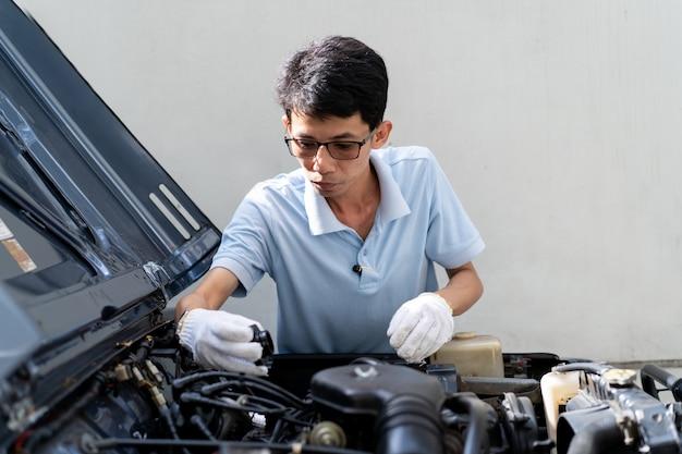 Человек, заправка двигателя крупным планом. концепция безопасного вождения и ухода за автомобилем.