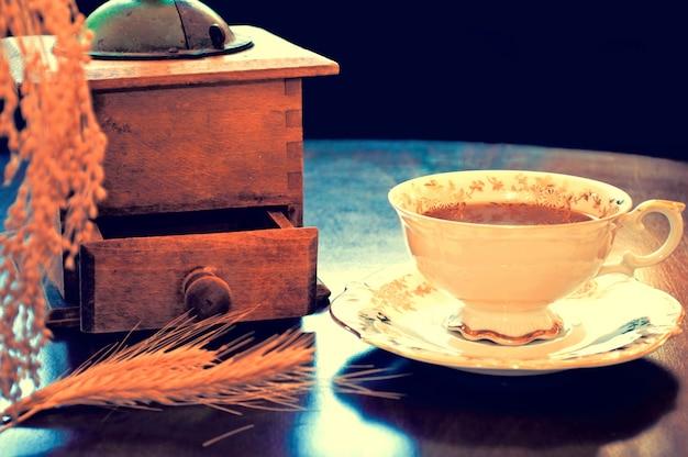 古いグラインダーとコーヒーのカップ
