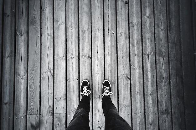 Человек, стоящий на старом деревянном полу.