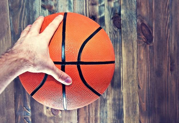 Баскетбольный мяч на деревянном паркетном полу, захватившем руку.