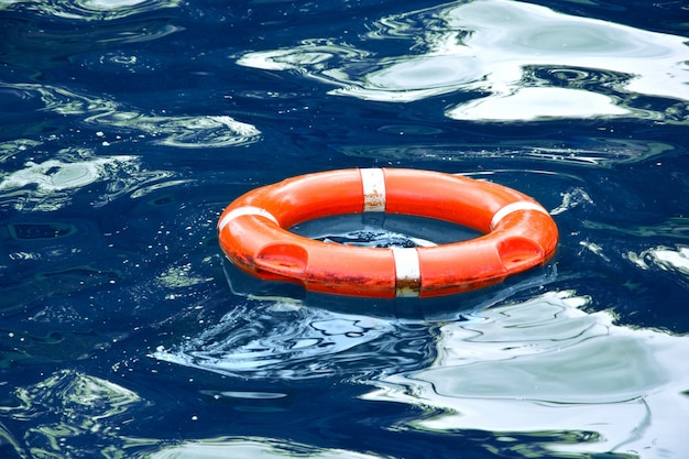Красный спасательный круг в голубой воде.