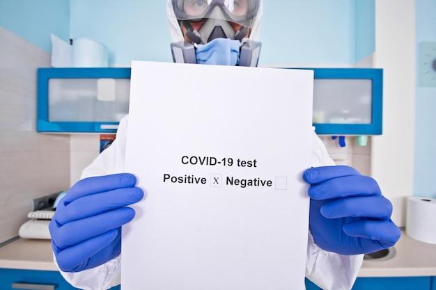 防護服の制服を着た医師とマスクがコロノウイルスの検査結果を保持しています。