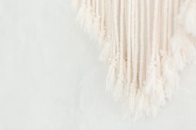 ミニマルなスカンジナビアの壁に綿のマクラメパネルフリンジのクローズアップ。