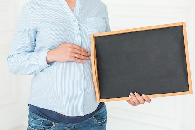 Беременная женщина держит пустую доску