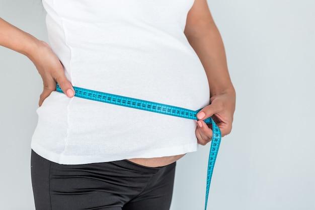 妊娠中の女性は、薄い青色の背景に分離された巻尺で彼女のおなかを測定します。