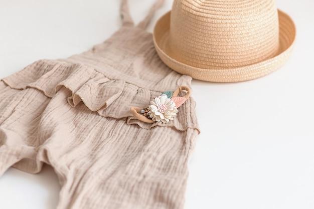 女の子、スタイリッシュなロンパーススーツ、麦わら帽子、花のアクセサリーの夏の子供服のセット。