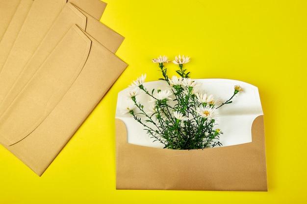 春のフラワーアレンジメントと金の封筒