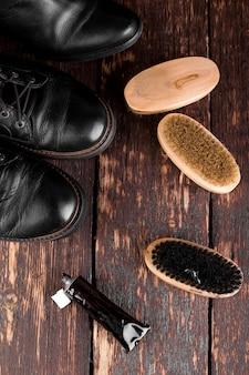 研磨装置、ブラシ、ポリッシュクリームが付いた木製の表面に黒いブーツ、