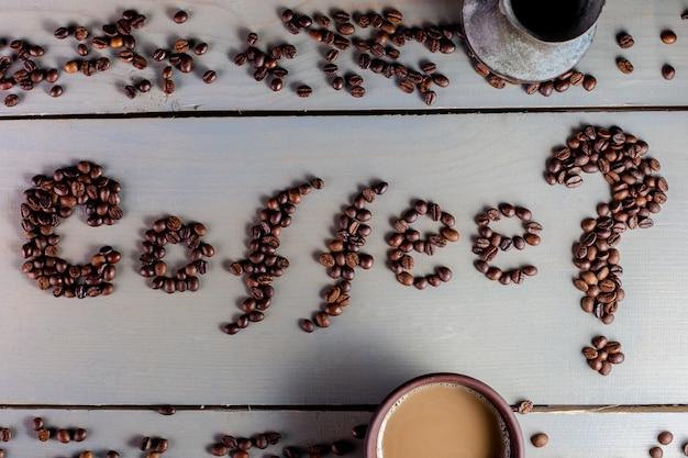 カップ近くのテーブルでコーヒーという言葉、