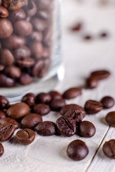 コーヒー豆または白い木製の表面に瓶に穀物