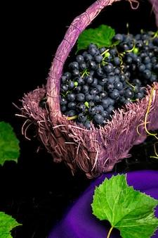 ブラックの表面にバイオレットバスケットで赤ワインのブドウ、
