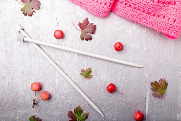 灰色の表面に編み針の近くのピンクのスカーフ、