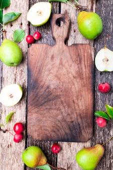 空のまな板の周りの梨と小さなリンゴ
